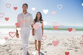 Beautiful couple holding hands and walking towards camera against valentines heart design