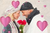 Smiling couple in winter fashion posing with roses against parchment
