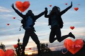 Silhouette couple jumping against the sky against valentines love hearts
