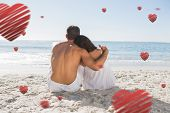 Couple sitting on the sand watching the sea against hearts
