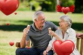 Senior couple eating an ice cream on a bench against hearts