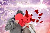 Happy mature couple in winter clothes holding red heart against digitally generated pretty flower background