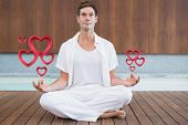 Handsome man in white meditating in lotus pose against pink hearts