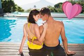 Couple sitting by swimming pool on a sunny day against heart