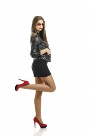 pic of posh  - Young beautiful woman posing in black leather jacket dark shorts and red high heels shoes over white background - JPG