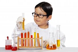 stock photo of chemical reaction  - Portrait of little scientist holding beaker and looking the reaction isolated over white - JPG