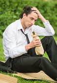 foto of unemployed people  - Frustrated unemployed man sitting at the lawn and drinking alcohol - JPG