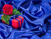 pic of blue rose  - Red gift box with blue bow and rose surrounded by dark blue silk fabric - JPG