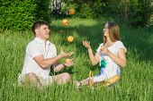 image of juggling  - The young man juggling apples with girl during a picnic in a city park - JPG