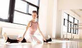 stock photo of leg-split  - Smiling Pretty Young Ballerina Splitting her Legs For Warm Up on the Floor Inside the Studio - JPG