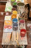 stock photo of pottery  - Work table of a pottery decorator of Caltagirone with different color containers and paintbrushes - JPG