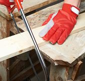 pic of sawing  - Sawing wooden pine board with the hand saw indoor composition - JPG