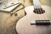image of ukulele  - Close up of ukulele on old wood background with soft light Vintage tone - JPG