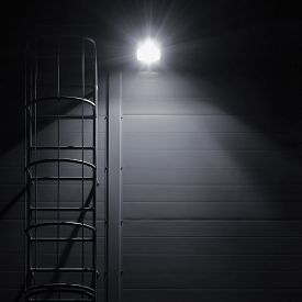 stock photo of stairway  - Fire emergency rescue access escape ladder stairway roof maintenance stairs at night bright shining lantern lamp light illumination glow shadows rustic textured industrial building wall panels texture pattern large detailed vertical closeup copy space bac - JPG