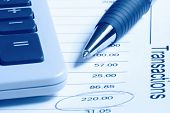 A ballpoint pen and calculator on a financial statement.  Blue duotone.