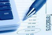 Ein Kugelschreiber und Taschenrechner auf einer Finanzaufstellung.  Blaue Duotone.