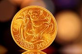 A gold Australian $200 coin, with a colorful light background.  Commemorative, uncirculated coin.