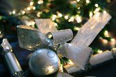 Christmas decorations ~ silver balls, ribbons and crackers, with fairy light background.