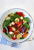Salad of roasted vegetables, kidney beans, spinach, and goat's cheese.  In old enamel bowl.