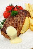 Grilled beef steak with potato wedges, cherry truss tomatoes, and bearnaise sauce.  Garnished with p