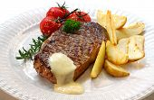 Grilled New York strip steak with bearnaise sauce, potato wedges, and cherry truss tomatoes.  Garnis