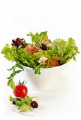 Greek salad in white bowl.  Mixed lettuce, red onion, cherry tomatoes, goat's cheese, black olives a