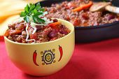 Bowl of chili with beans, with cooking pan behind.  Delicious chili con carne.