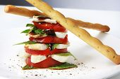 Caprese salad in a stack, with bread sicks.  Tomato and basil salad, with baby mozzarella and balsam