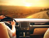 Male hands on car steering wheel. View from car windshield to road and beautiful landscape. poster