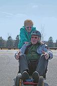 Senior Woman Giving Boost To Senior Man On Skateboard!