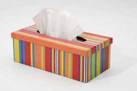 stock photo of tissue box  - Colorfull tissue box with a white tissue sticking out of the box - JPG