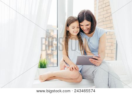 poster of People, Technology, Family, Children Concept. Positive Young Other And Her Small Daughter Sit On Win