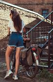 Sexy Slim Girl Wearing Short Denim Shorts And A White T-shirt Walking With A City Bicycle Near An Ol poster