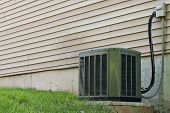 foto of hvac  - A residential central air conditioning unit sitting outside a home used for regulating the homes AC to a comfortable level - JPG