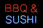 Red and blue neon sign of the words 'BBQ & SUSHI' on a black background.