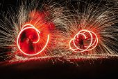 Fire Dancers Swing, Spinning Red Fire And Man Juggling With Bright Sparks In The Night. Fire Show Pe poster