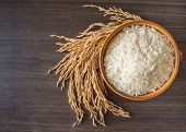 Raw White Rice (thai Jasmine Rice)  In Brown Bowl And And Ear Of Rice Or Unmilled Rice On Wooden Bac poster