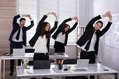 Happy Businesspeople Doing Stretching Exercise Behind Desk At Workplace poster
