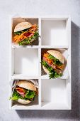 Homemade Mini Burgers With Ham, Tomato, Carrot, Fresh Salad Served In Old White Wooben Box On Gray B poster