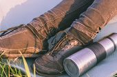 Thermal Flask With Tea Laying On The Tourists Mat Near To The Travelers Feet In Black Trainers. Conc poster