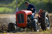 pic of chug  - Old Tractor ploughing field in rural countryside - JPG