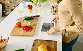 Healthy Food Concept. Woman Looking For Recipe Vegetarian Food On The Internet. Woman Cooking Health poster