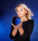 Jovem e bela mulher com bola de cristal.
