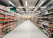 Abstract Blurred Supermarket Aisle With Colorful Shelves And Unrecognizable Customers As Background poster