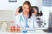 Stressed Female Medical Doctor Sitting At Office Table And Holding Hands Near Head