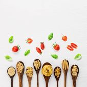 Different Kind Of Pasta On Wooden Spoon And Ingredients On White Background From Top View. Italian F poster
