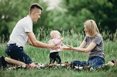 Happy Family Enjoy Weekend In Nature. Loving Parents Watch Their Daughter Doing First Steps. Baby Le poster