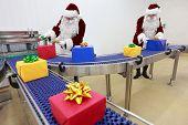 Zwei Weihnachtsmänner in Produktion - Herstellung Geschenksideen, übernehmen sie arbeiten.