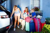 Mother, Girl And Boy Are Loading Multicolored Suitcases In The Trunk Of Car. Family With A Dog Labra poster