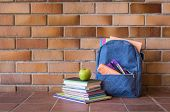Blue backpack with school supplies against brick wall. Full school bag with books and notebooks in a poster